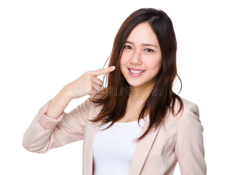 Affärskvinnafingerpunkt till hennes tänder arkivbild