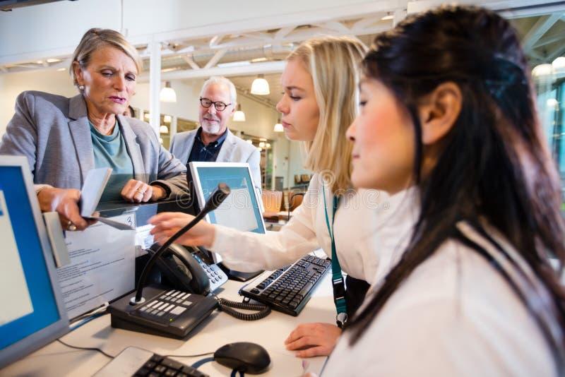 AffärskvinnaGiving Passport To personal på skrivbordet i flygplats arkivbilder