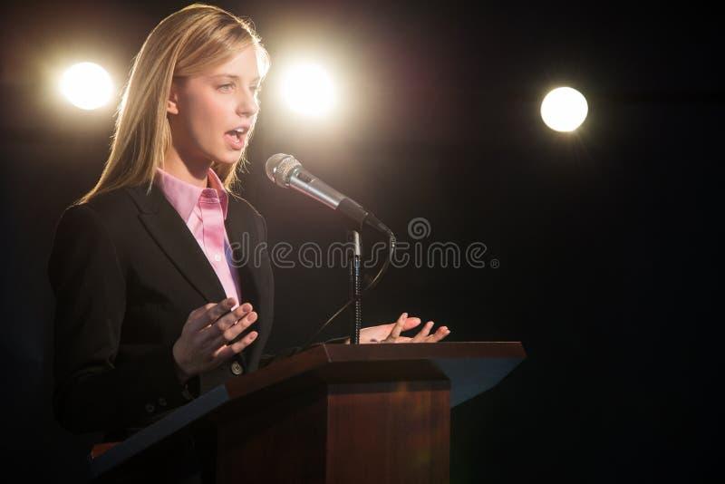 AffärskvinnaGiving Speech At podium i salong royaltyfri bild