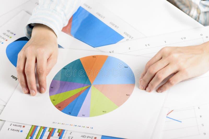 Affärskvinnahänder som analyserar finansiell statistik arkivfoto