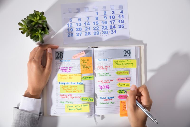 AffärskvinnaHand ` s med kalenderhandstilschema i dagbok arkivfoto