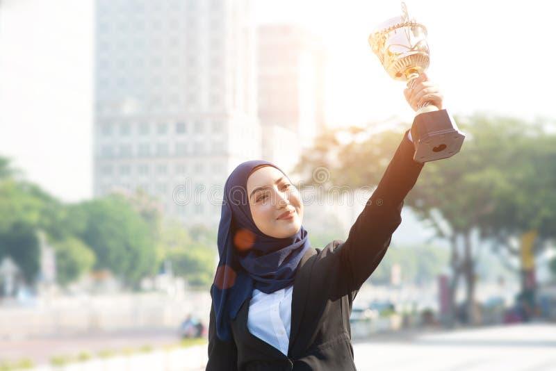 Affärskvinnahand som rymmer en trofé arkivbilder