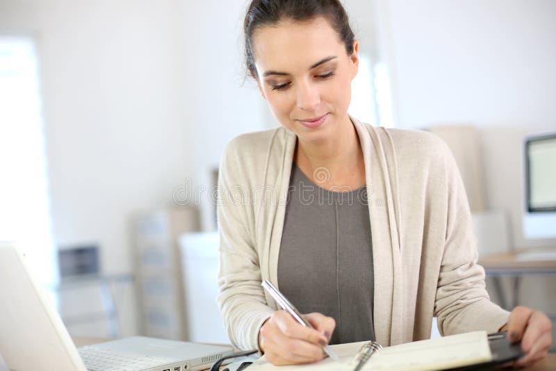 Affärskvinnahandstil i dagordning royaltyfri foto