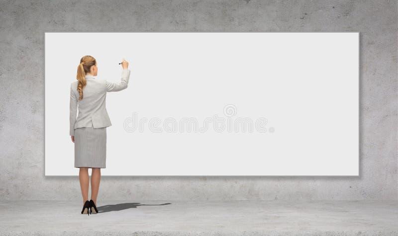 Affärskvinnahandstil med markören på det vita brädet arkivbilder