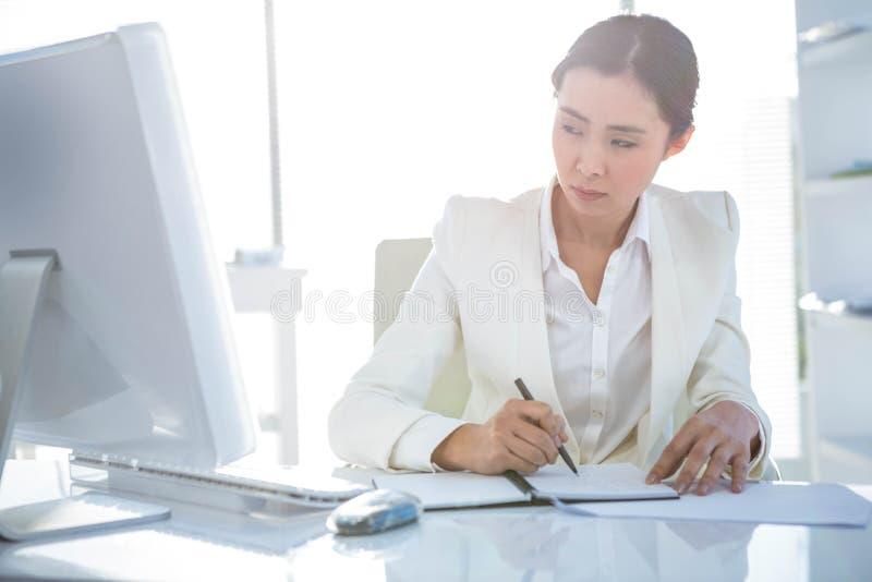 Affärskvinnahandstil på dagboken på skrivbordet royaltyfria bilder