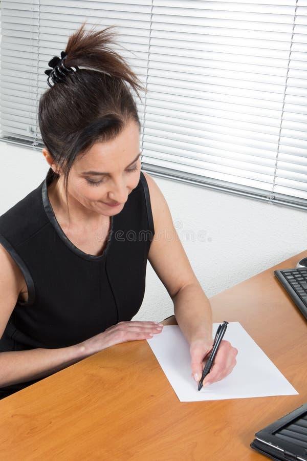 Affärskvinnahandstil på pappers- undertecknande avtalsdokument i skrivbord arkivfoton
