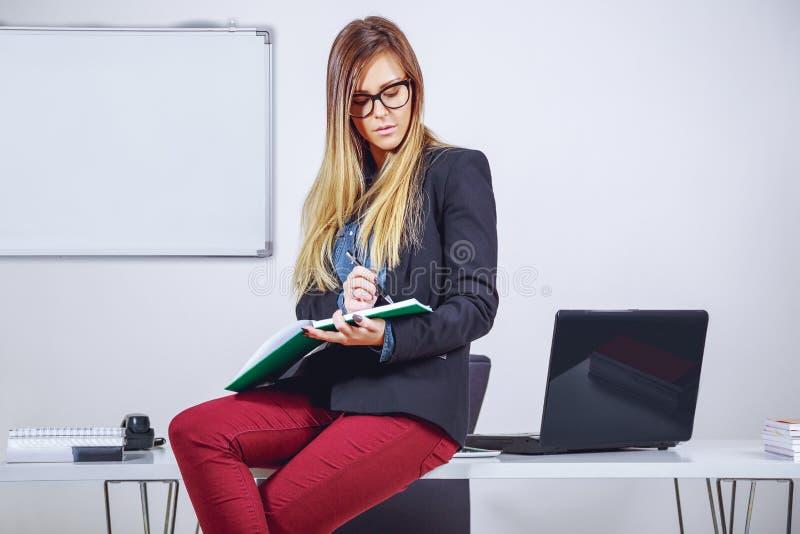 Affärskvinnahandstilanmärkningar och sammanträde på skrivbordet royaltyfri foto