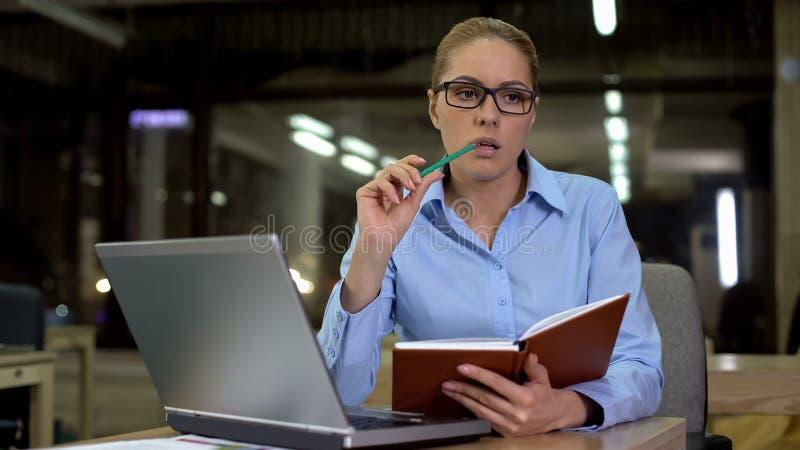 Affärskvinnahandstilidéer in i anteckningsboken som planerar nästa arbetsdags, dagordning royaltyfri fotografi