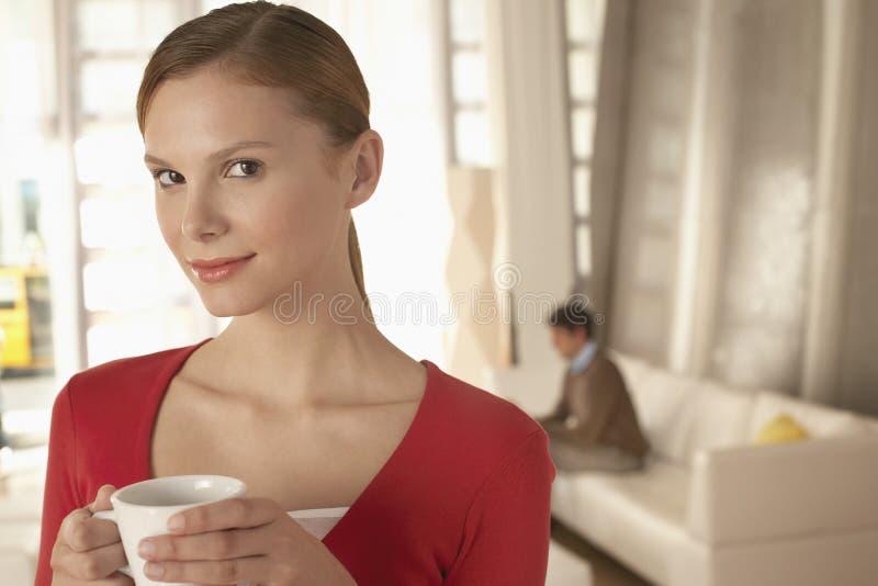 AffärskvinnaHolding Coffee Cup i regeringsställning lobby arkivfoto