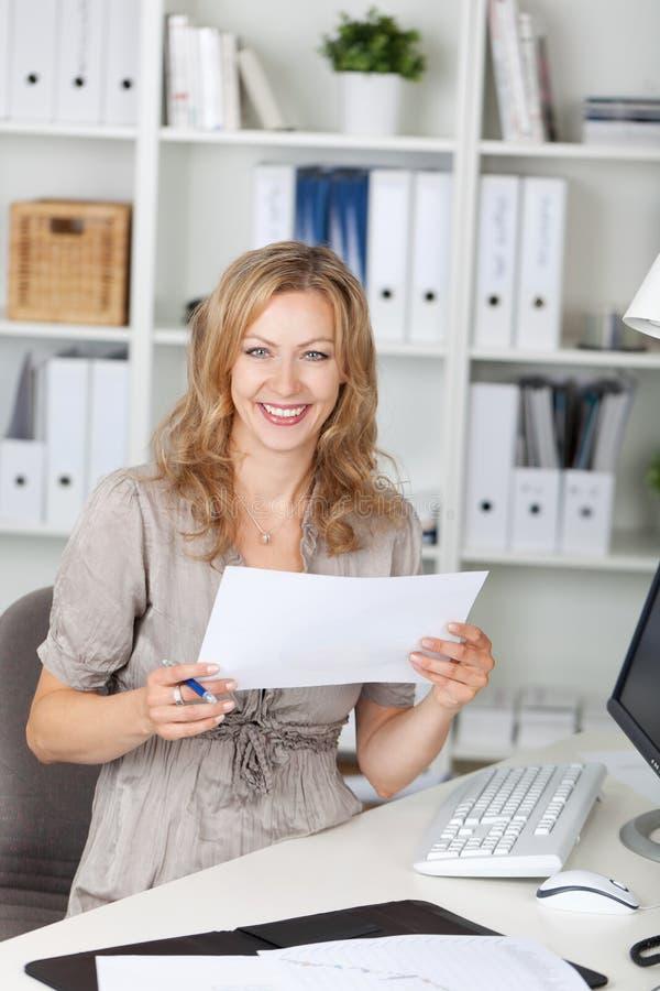 AffärskvinnaHolding Paper While sammanträde på stol på kontoret royaltyfria bilder
