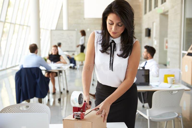 AffärskvinnaIn Office Preparing packe för sändning arkivbilder