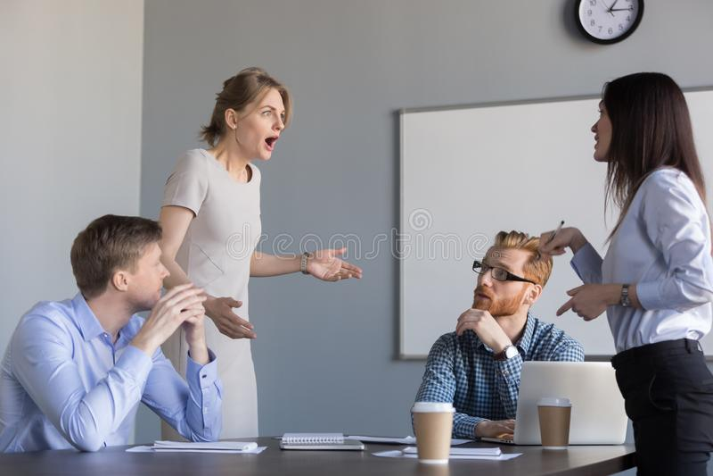 Affärskvinnakollegor som grälar på mötet för företags kontor, royaltyfri fotografi