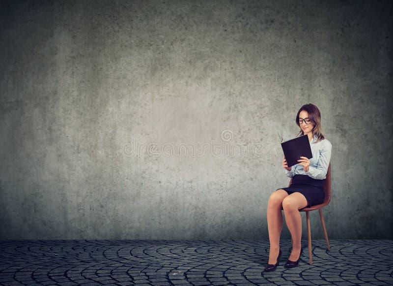 Affärskvinnaläsebok på stol royaltyfri fotografi