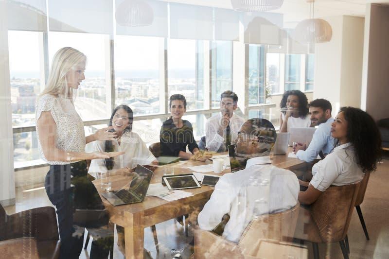 AffärskvinnaLeads Meeting Around tabell som skjutas till och med dörr royaltyfria bilder
