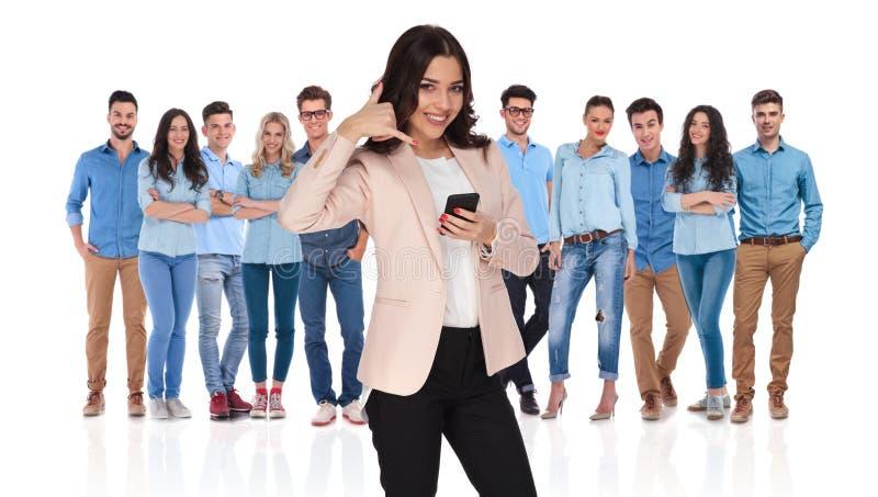 Affärskvinnaledaren med telefonen önskar att du ska kalla hennes grupp arkivfoton