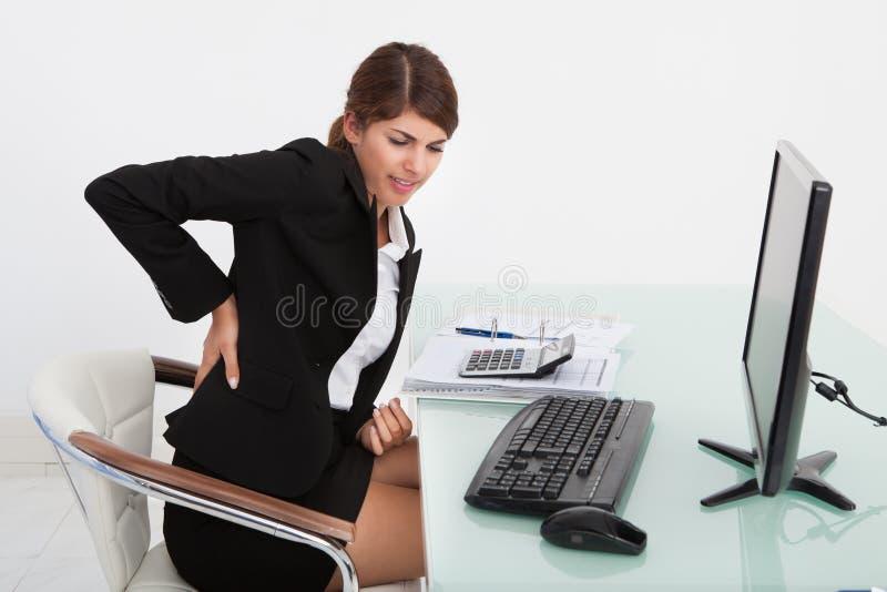 Affärskvinnalidande från ryggvärk på datorskrivbordet royaltyfri foto