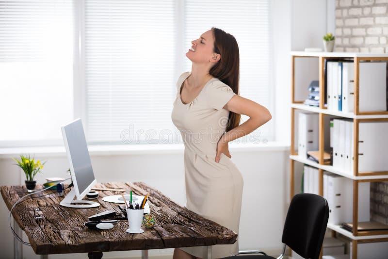 Affärskvinnalidande från tillbaka smärtar arkivfoto