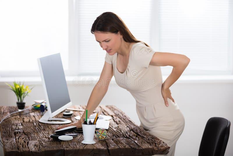 Affärskvinnalidande från tillbaka smärtar arkivbild