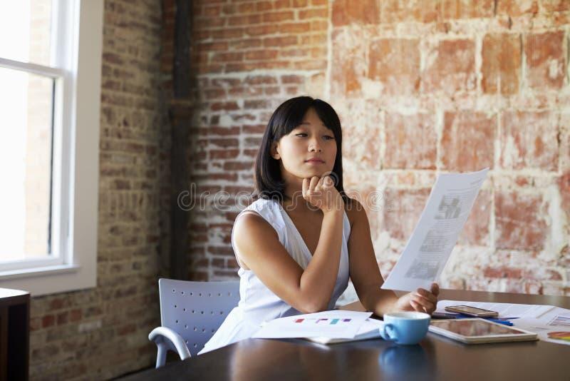 AffärskvinnaMaking Notes On dokument i styrelse royaltyfri foto