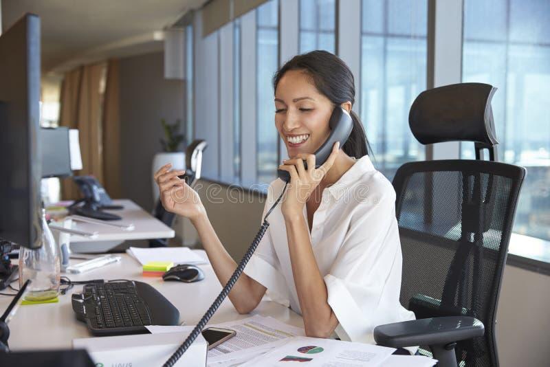 AffärskvinnaMaking Phone Call sammanträde på skrivbordet i regeringsställning royaltyfri fotografi