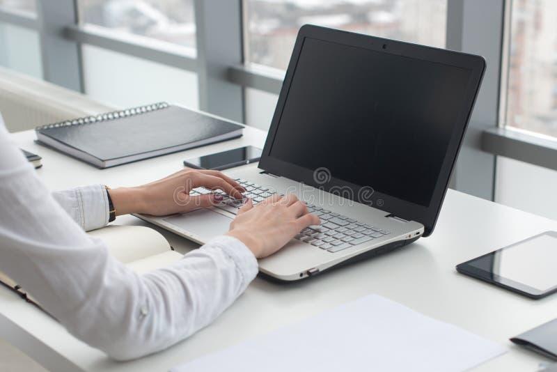 Affärskvinnamaskinskrivning på bärbara datorn på arbetsplatskvinnan som i regeringsställning arbetar handtangentbordet arkivbild