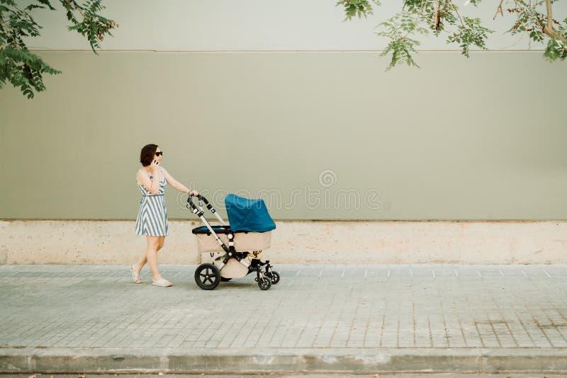 Affärskvinnamodern och ditt behandla som ett barn i vagnen som går på den stads- trottoaren - materielfoto arkivfoton