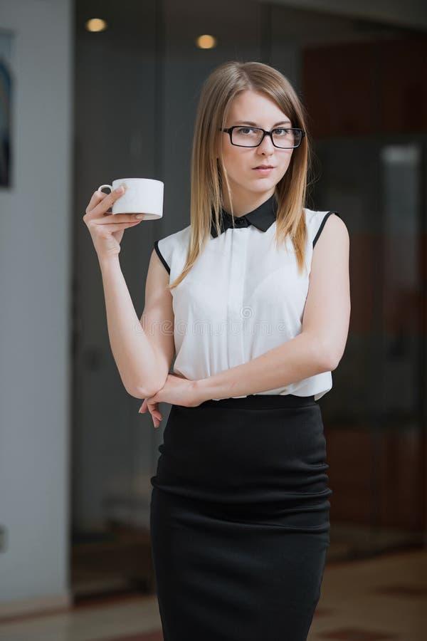 Affärskvinnan är i hennes kontor med en kopp av varmt kaffe royaltyfria bilder