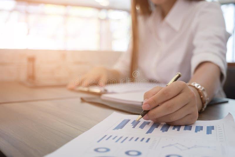 Affärskvinnan analyserar marknadsdiagrammet på arbetsplatsen ung kvinnligen royaltyfria foton