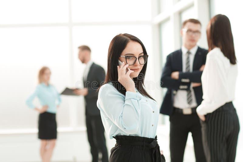 Affärskvinnan använder mobiltelefonen för affärskonversation royaltyfri foto