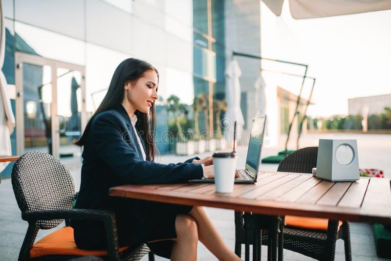 Affärskvinnan arbetar på bärbara datorn i regeringsställning arkivfoto