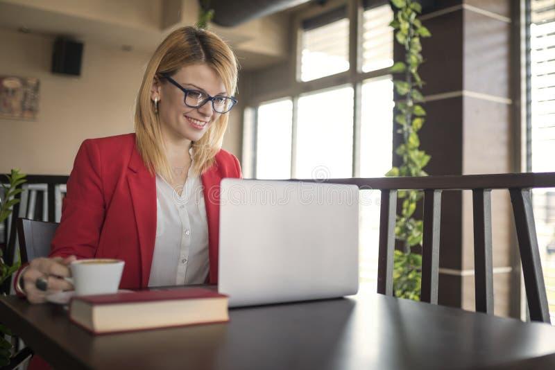 Affärskvinnan arbetar på bärbara datorn och dricker koppen kaffe och exponeringsglas av vatten i coffee shop, restaurang royaltyfria foton