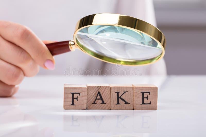 Affärskvinnan Examining Blocks Showing fejkar ord royaltyfria bilder