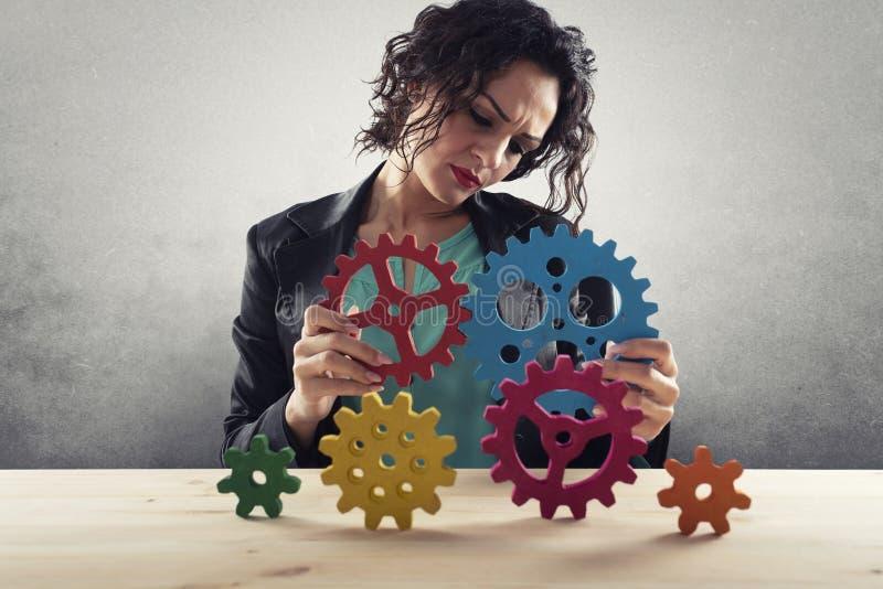 Affärskvinnan försöker att förbinda kugghjulstycken Begrepp av teamwork, partnerskap och integration fotografering för bildbyråer