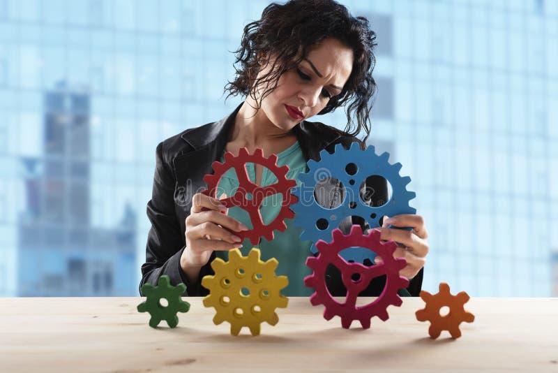 Affärskvinnan försöker att förbinda kugghjulstycken Begrepp av teamwork, partnerskap och integration arkivbilder