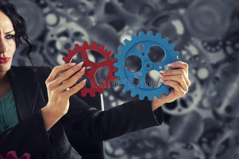 Affärskvinnan försöker att förbinda kugghjulstycken Begrepp av teamwork, partnerskap och integration arkivbild