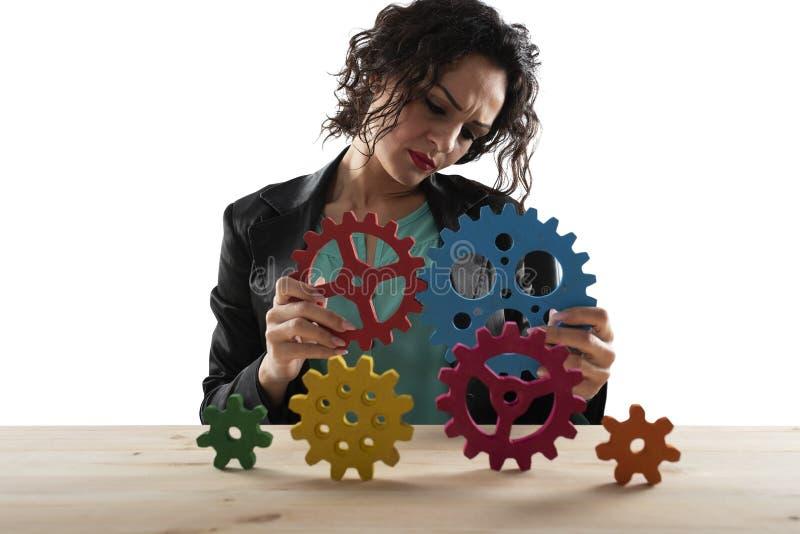 Affärskvinnan försöker att förbinda kugghjulstycken Begrepp av teamwork, partnerskap och integration royaltyfria foton