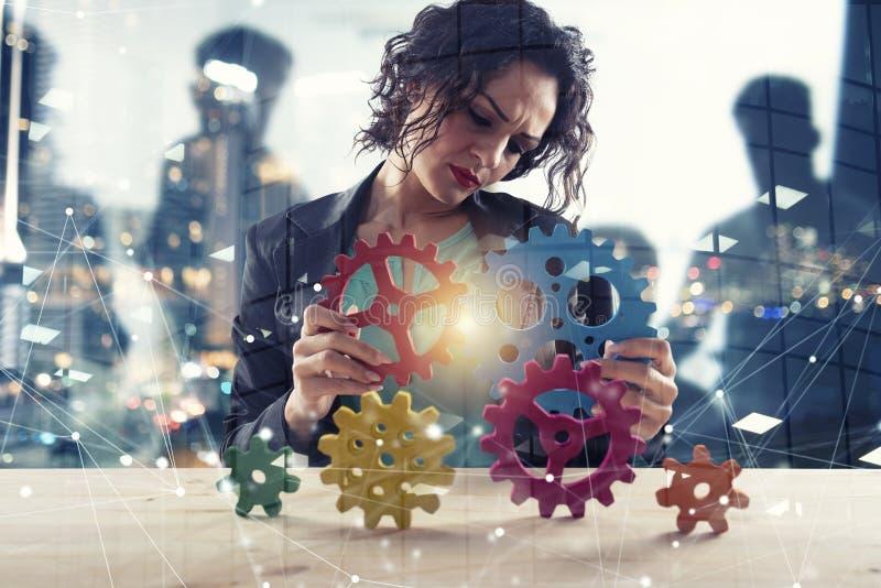 Affärskvinnan försöker att förbinda kugghjulstycken Begrepp av teamwork, partnerskap och integration dubbel exponering royaltyfri fotografi