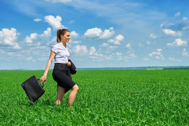 Affärskvinnan går på det utomhus- fältet för grönt gräs Iklädd dräkt för härlig ung flicka, vårlandskap, ljus solig dag royaltyfri foto