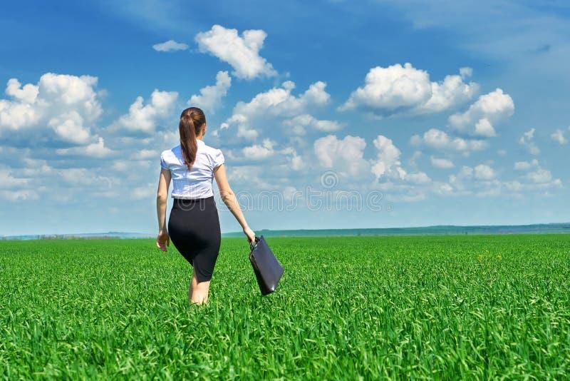 Affärskvinnan går på det utomhus- fältet för grönt gräs Iklädd dräkt för härlig ung flicka, vårlandskap, ljus solig dag arkivfoto