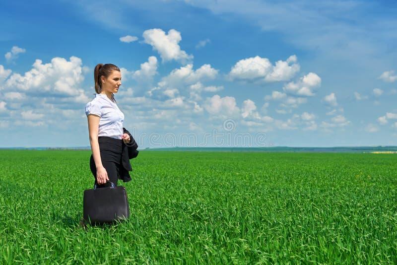 Affärskvinnan går på det utomhus- fältet för grönt gräs Iklädd dräkt för härlig ung flicka, vårlandskap, ljus solig dag royaltyfri fotografi