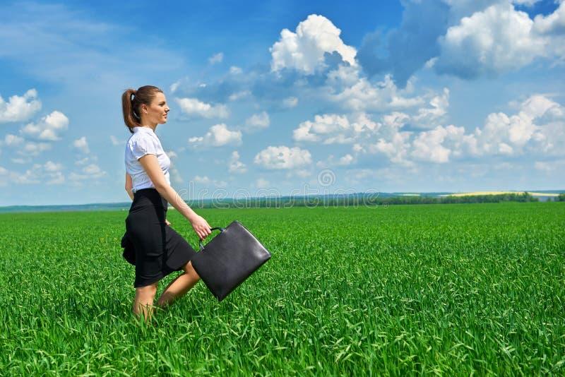 Affärskvinnan går på det utomhus- fältet för grönt gräs Iklädd dräkt för härlig ung flicka, vårlandskap, ljus solig dag arkivbilder