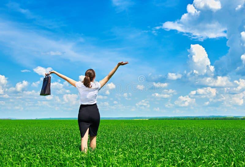 Affärskvinnan går på det utomhus- fältet för grönt gräs och kopplar av under solen Iklädd dräkt för härlig ung flicka som vilar,  royaltyfri fotografi