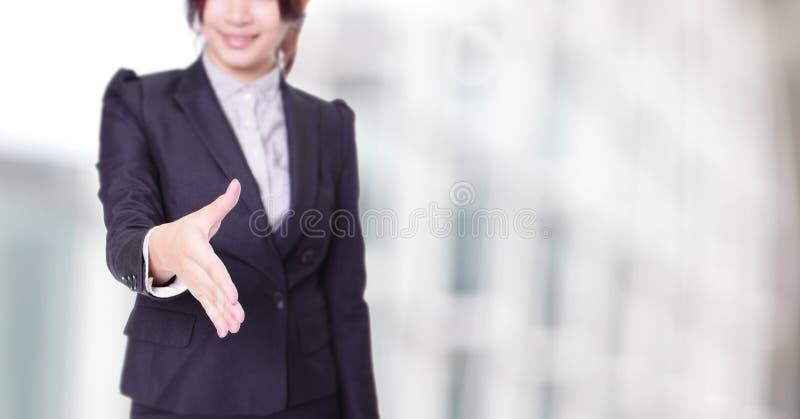 Affärskvinnan ger en handskakning med leende royaltyfri bild