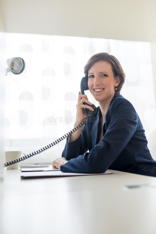 Affärskvinnan i blått passar kalla någon till och med telefonen royaltyfri foto