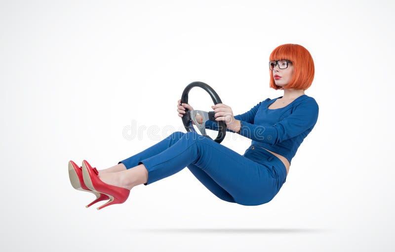 Affärskvinnan i blått passar och exponeringsglaschaufförbilen med ett styrninghjul arkivfoton