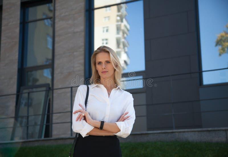 Affärskvinnan i en dräkt korsade hennes armar över hennes bröstkorg mot av kontorsbyggnad arkivbild