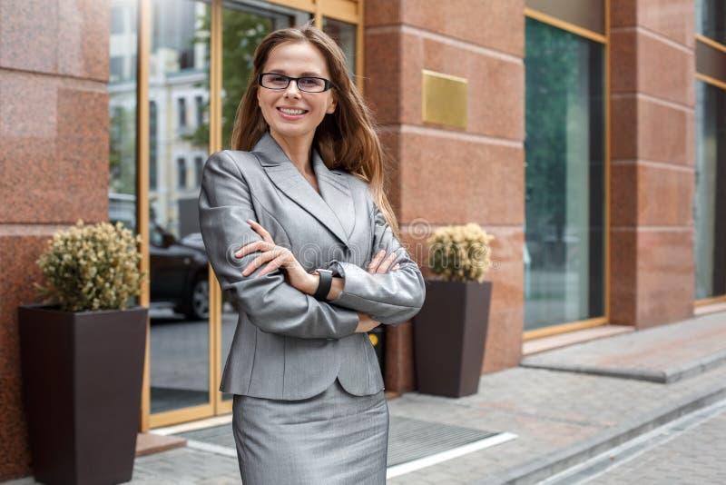 Affärskvinnan i glasögon som står på stadsgatan, korsade armar som ser den gladlynta kameran royaltyfri bild