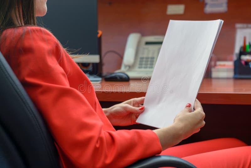 Affärskvinnan i röd dräkt sitter i en läderstol och läsning ett avtal som kontrollerar papperet fotografering för bildbyråer
