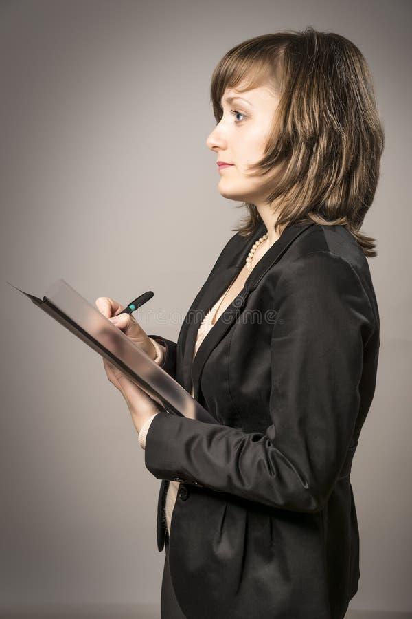 Affärskvinnataken noterar royaltyfri bild