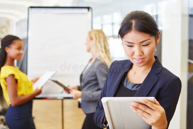 Affärskvinnan kontrollerar affärsplan med minnestavlan arkivbilder